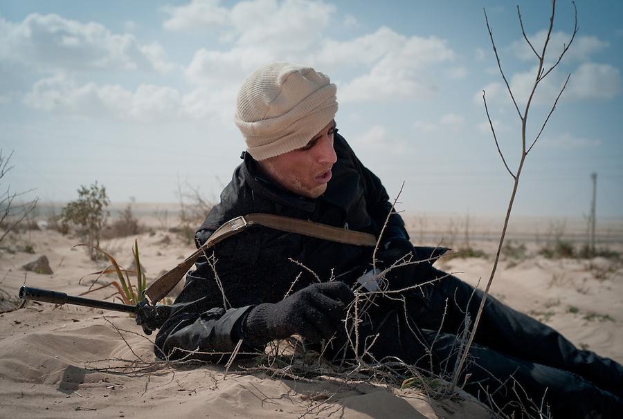 Rebel fighter rests in desert near Ajdabiya, Libya.