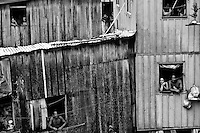 People watch out of their windows in a shanty town of Manaus, Brazil, 2 April 2004. Amazonia is the world's largest dense tropical forest area. Since the 16th century the original indigenous people have been virtually pushed away or exterminated. The primal ancient unity between tribes and the jungle ambient has changed into a fight between the urban based civilization and the jungle enviroment. Although new generations of white and mestizo settlers have not become adapted to the wild tropical climate and rough conditions, they keep moving deeper into the virgin forest. The technological expansion causes that Amazonia is changing rapidly.