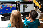 Preschool classroom two girls sitting side by side playing learning games on computers