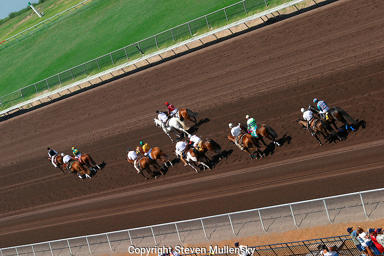Out riders escort the jockeys along the back stretch on the way to the starting gate.