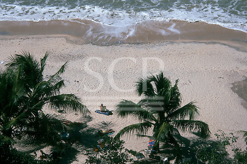 Pipa, Northeast Brazil. Looking down on unspoilt beach with palm trees, white sand and people sunbathing by the sea.