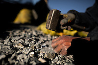 A woman miner grinds the gold ore bearing rock with a hammer in the gold mines of La Rinconada, Peru, 3 August 2012. During the last decade, the rising price of the gold has attracted thousands of people to La Rinconada in the Peruvian Andes. At 5300 metres above sea level, nearly 50.000 people work in the gold mines and live in the nearby colonies without running water, sewage system or heating service. Although the work in the mines is very dangerous (falling rocks, poisonous gases and a shifting glacier), the majority of miners have no contract and operate under the cachorreo system - working 30 days without payment and taking the gold they supposedly find the 31st day as the only salary. In spite of a demaged environment, caused by mercury contamination from the mining and the lack of garbage disposal, people continue to flock to the region hoping to find their fortune.