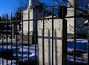 Old weathered headstones behind an iron fence in an scenic New England graveyard,