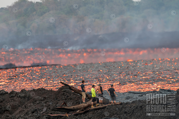 June 2018: Four spectators contemplate a massive lava river in Lower Puna, Big Island of Hawai'i. The river is up to 300 yards wide, with Green Mountain in the distance.