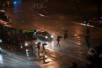 Pedestrians running across a road, through the rain, in central Belgrade..