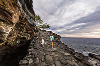 A woman and her dog hike along the historic 1871 Trail in Honaunau, Big Island. This trail was the main artery for coastal travel in the area, connecting several villages along its length.
