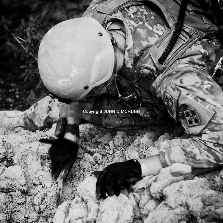 1LT Brien from 1 Platoon, Delta Co, 1-66, 4th Infantry Division, searches for arms caches and IEDs around Jazah village in the  Arghandab Valley, Kandahar, 03 May 2011. (John D McHugh)
