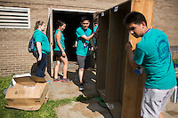 """Members move a bookshelf to a dumpster during """"Circle the City with Service,"""" the Kiwanis Circle K International's 2015 Large Scale Service Project, on Wednesday, June 24, 2015, at the Friendship Westside Center for Excellence in Indianapolis. (Photo by James Brosher)"""
