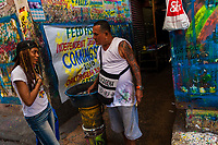 "José Corredor (""Runner"") talks with a girl while clearing paint from his brushes in the sign painting workshop in Cartagena, Colombia, 14 April 2018. Hidden in the dark, narrow alleys of Bazurto market, a group of dozen young men gathered around José Corredor (""Runner""), the master painter, produce every day hundreds of hand-painted posters. Although the vast majority of the production is designed for a cheap visual promotion of popular Champeta music parties, held every weekend around the city, Runner and his apprentices also create other graphic design artworks, based on brush lettering technique. Using simple brushes and bright paints, the artisanal workshop keeps the traditional sign painting art alive."