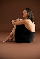 Young Hispanic woman siting sideways with arms around her legs