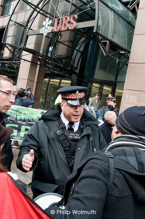 A City of London police constable asks Alberto Durango, a member of UNITE and the Latin American Workers Association, to move away from the London headquarters of Swiss bank UBS, where he worked as a cleaner until being sacked by contractor Lancaster Cleaning and Support Services following a campaign for improved pay and conditions.