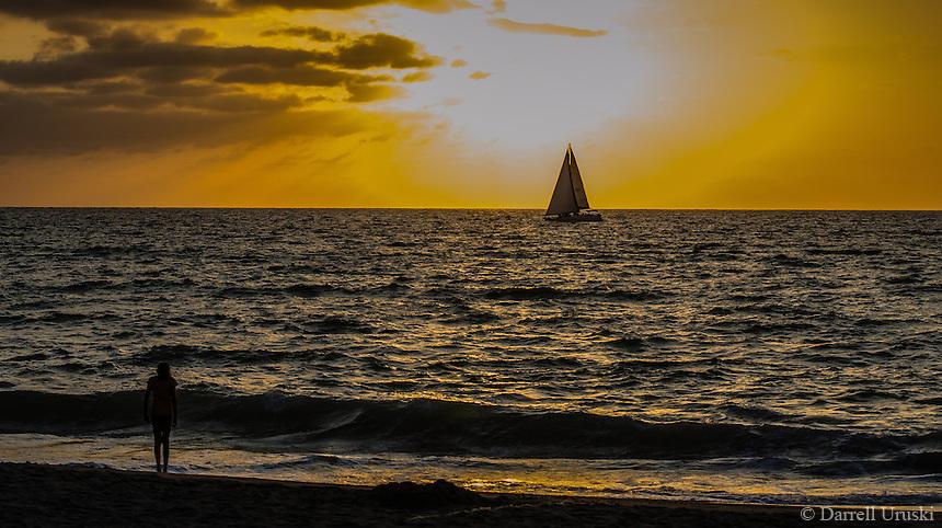 Fine Art Landscape Photograph, Sunset in Banderas Bay, Puerto Vallarta, Mexico. Sailboat passes by the setting sun.