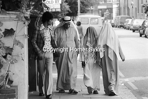 Arabs London UK 1977. Middle Eastern people came to Britain for subsidised health care in Harley Street clinics. They mainly stayed in the Earls Court area. Arab woman shopping in chemist shop.