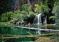 12 year old boy walking on log in middle of mountain lake. Colorado United States Hanging Lake.