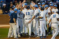 Dustin Ackley #13 of the North Carolina Tar Heels is congratulated by his teammates following his first inning home run versus the Duke Blue Devils at Durham Bulls Athletic Park May 20, 2009 in Durham, North Carolina.  (Photo by Brian Westerholt / Four Seam Images)