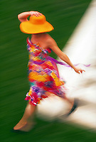 Blurred motion image of a woman wearing a brightly colored dress and sunhat and walking.