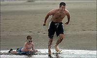 A boy and his father (both model released) play in the ocean along a South Carolina beach.  Photo taken on Sullivan's Island, near Charleston, South Carolina beach on the Atlantic Ocean, but could represent a beach scene anywhere.