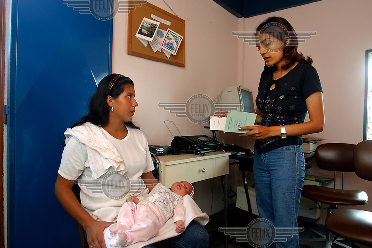 Only 15 years old, holding her baby, a newly arrived Colombian refugee receives information and documents from an NGO working to improve conditions for refugees.