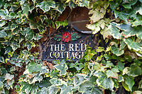 BNPS.co.uk (01202) 558833. <br /> Pic: SandersonYoung/BNPS<br /> <br /> The Red Cottage sign.<br /> <br /> A quirky 'show home' for a brickwork owner where Lewis Carroll is believed to have stayed while writing some of his Alice in Wonderland books is on the market for just under £1m.<br /> <br /> Red Cottage is a striking Grade II listed property in Whitburn, Tyne and Wear, where Charles Dodgson, otherwise known as Lewis Carroll, regularly visited family.<br /> <br /> The unusual 179-year-old home was built to show off as many design features as possible, and has a walled garden and even an air raid shelter.