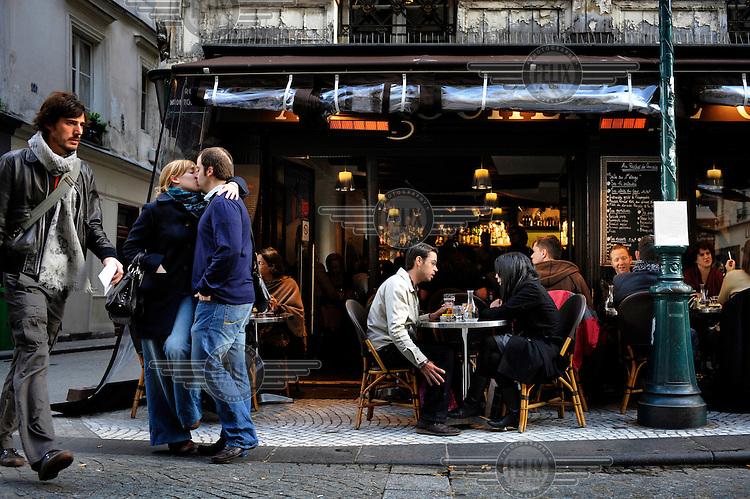 A couple kiss as they leave Au Rocher de Cancale restaurant in Paris.