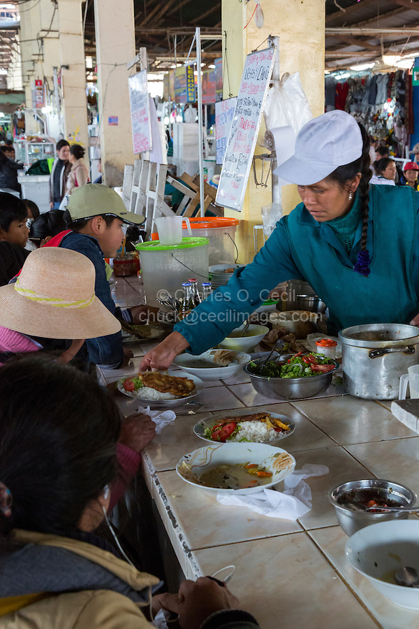 Peru, Cusco, San Pedro Market.  Cook Serving a   Customer Eating in the Food Court Area of the Market.