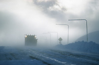 Snow plow navigates the high winds and blowing snow on the Steese Highway, Eagle Summit, Alaska