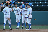 Kevin Kramer (7), Brett Stephens (23), and Ty Moore (29) of the UCLA Bruins greet teammate Luke Persico (21) after Persico's home run during a game against the Hofstra Pride at Jackie Robinson Stadium on March 14, 2015 in Los Angeles, California. UCLA defeated Hofstra, 18-1. (Larry Goren/Four Seam Images)