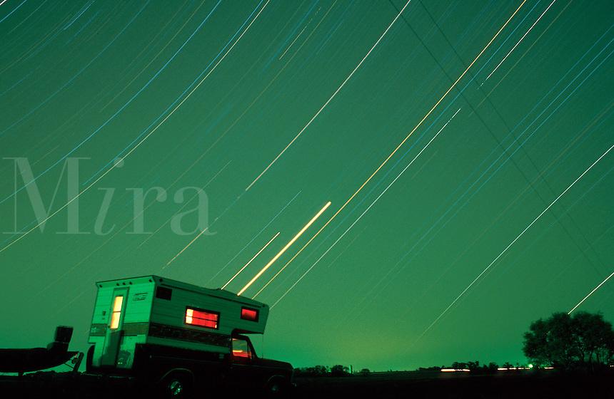 RV illuminated at night with star trails.