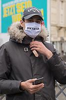 """Sogenannten """"Querdenker"""" sowie verschiedene rechte und rechtsextreme Gruppen hatten fuer den 18. November 2020 zu einer Blockade des Bundestag aufgerufen. Sie wollten damit verhindern, dass es eine Abstimmung ueber das Infektionsschutzgesetz gibt.<br /> Es sollen sich ca. 7.000 Menschen versammelt haben. Sie wurden durch Polizeiabsperrungen daran gehindert zum Reichstagsgebaeude zu gelangen. Sie versammelten sich daraufhin u.a. vor dem Brandenburger Tor.<br /> Im Bild: Ein Demonstrant mit einem Mund-Nase-Schutz mit der Aufschrift """"Diktatur"""".<br /> 18.11.2020, Berlin<br /> Copyright: Christian-Ditsch.de"""