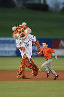 Lakeland Flying Tigers mascot Southpaw races a young fan for an on field promotion in between innings during a game against the Tampa Yankees on April 9, 2015 at Joker Marchant Stadium in Lakeland, Florida.  Tampa defeated Lakeland 2-0.  (Mike Janes/Four Seam Images)