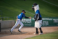 Missoula Osprey center fielder Alek Thomas (19) gets a high five from Ollie Osprey before a Pioneer League game against the Grand Junction Rockies at Ogren Park Allegiance Field on August 21, 2018 in Missoula, Montana. The Missoula Osprey defeated the Grand Junction Rockies by a score of 2-1. (Zachary Lucy/Four Seam Images)