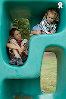 Boy (11-13) and girl (5-7) playing in plastic cube (Licence this image exclusively with Getty: http://www.gettyimages.com/detail/73532606 )