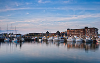Lobster Boats rest at Newport Rhode Island's State Pier at sunset, overlooking Long Wharf Resorts in background.
