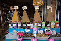 """Essaouira, Morocco.  Vendor of Spices and Herbal Medicines Setting up Shop in early Morning.  Note """"Viagra Turbo"""", Feminine Aphrodisiac, and Herbs for Losing Weight."""