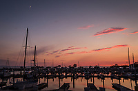 The waxing crescent moon looks down on a sunset scene at the San Leandro Marina along San Francisco Bay on a summer evening.