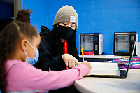 Mentor Carlee Rogel helps Jayla Hall, 7, at the Boys and Girls Club of Western Pennsylvania in the Lawrenceville neighborhood on Friday February 19, 2021 in Pittsburgh, Pennsylvania. (Photo by Jared Wickerham/Pittsburgh City Paper)