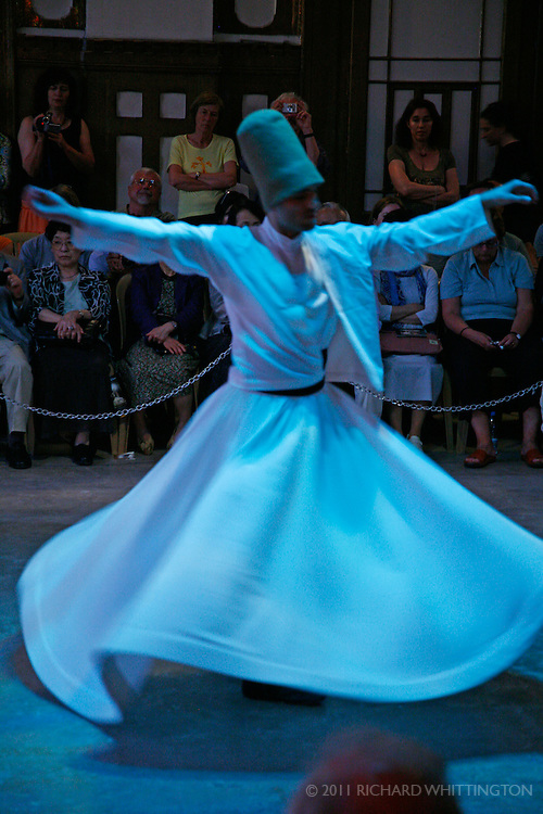 A whirling dervish's white skirt flies out as he turns and dances as part of the Sema Ritual.