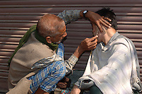Getting a Shave on the streets of New Delhi, India.