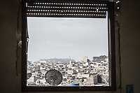 In this Friday, Oct. 26, 2012 photo. At the first day of Aid celebration, Aleppo's Citadel is viewed from a window as mortar explosions and gun machine shoots sound at the battlefield in Karmal Jabl neighborhood in Alepppo City. (AP Photo/Narciso Contreras).