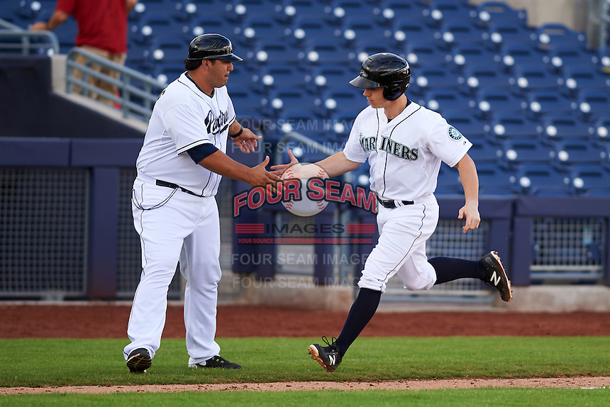 Peoria Javelinas outfielder Tyler O'Neill (4) congratulated by manager Rod Barajas (28) after hitting a walk off home run during an Arizona Fall League game against the Mesa Solar Sox on October 21, 2015 at Peoria Stadium in Peoria, Arizona.  Peoria defeated Mesa 5-3.  (Mike Janes/Four Seam Images)