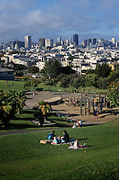 San Francisco, CA; Family Picnicing And Enjoying Afternoon Sun And City View At Mission Dolores Par