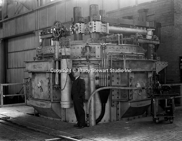 Client: Swindell Dressler Corporation<br /> Ad Agency: George Ketchum Advertising<br /> Contact: George Ketchum<br /> Product: Swindell Dressler Electric ARC Furnace<br /> Location: Swindell Dressler factory in Pittsburgh  <br /> <br /> Salesman demonstrating the new Swindell-Dressler Electric Arc Furnace at Swindell's manufacturing plant outside Pittsburgh.<br /> <br /> Swindell Dressler International Company was based in Pittsburgh, Pennsylvania. The company was founded by Phillip Dressler in 1915 as American Dressler Tunnel Kilns, Inc.  In 1930, American Dressler Tunnel Kilns, Inc. merged with William Swindell and Brothers to form Swindell-Dressler Corporation. The Swindell brothers designed, built, and repaired metallurgical furnaces for the steel and aluminum industries. The new company offered extensive heat-treating capabilities to heavy industry worldwide.