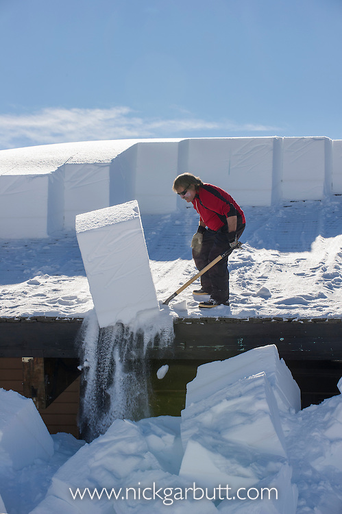 Jeff Henry clearing snow from roofs at Canyon Village. Yellowstone National Park, Wyoming, USA. January