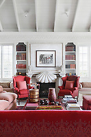 Crimson furniture and books add warmth to the cool, coastal themed whites of this living room suite