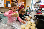 TORRINGTON,  CT-122519JS03- Nathan Matisoff, of New York City, looks on as his daughters Lilah, 5, and Emmy, 3, get rolls ready to put in the over as volunteers prep for the annual Christmas Day dinner Wednesday at the Torrington Soup Kitchen. <br /> Jim Shannon Republican-American