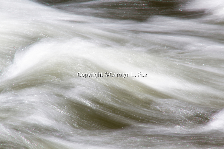 Water rushes over a rock on the Firehole River in Yellowstone National Park.