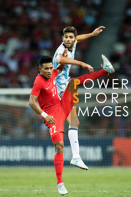 Khairul Nizam of Singapore (L) and  Federico Fazio of Argentina (R) who heads the ball during the International Test match between Argentina and Singapore at National Stadium on June 13, 2017 in Singapore. Photo by Marcio Rodrigo Machado / Power Sport Images