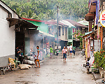 The smoke from a cooking fire drifts down a Sampaloc street.  Many of the homes on both sides are decorated for the home decorations contest later in the evening. (Sampaloc, Quezon Province, the Philippines)