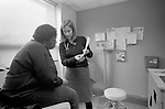Young female internal medicine resident physician talking with over-weight middle age African-American female patient on examination table in examination room