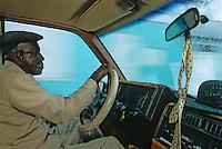 Iles Bahamas / New Providence et Paradise Island / Nassau: Chauffeur de taxi dans les rues de la ville un dimanche matin avant d'aller à la messe , la cravate est pendue au rétroviseur et le chapeau de son épouse est sur le tableau de bord